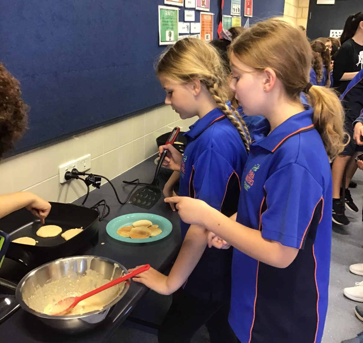 Students cooking banana pikelets